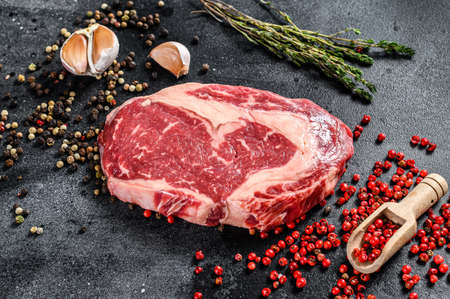 Photo pour Raw fresh marbled meat Steak Ribeye. Black Angus Rib eye with cooking ingredients. black background. top view. - image libre de droit