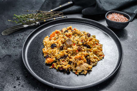 Photo pour Rice pilaf with lamb meat and vegetables in a plate. Black background. Top view. - image libre de droit