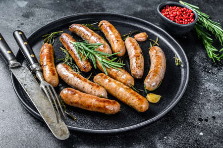 Photo pour Grilled sausages with rosemary herbs, beef and pork meat. Black background. Top view. - image libre de droit