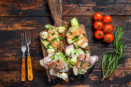 Foto de Smoked salmon and herring sandwich with cream cheese and salad on a cutting board. Dark wooden background. Top view. - Imagen libre de derechos