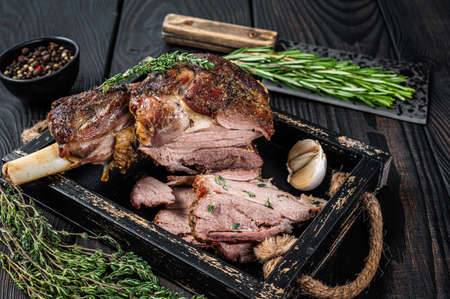 Photo pour Roasted mutton lamb leg sliced in a wooden tray with meat cleaver. Black wooden background. Top view - image libre de droit