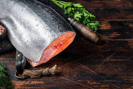 Photo pour Big piece of Raw cut salmon fish on a wooden cutting board with chef knife. Dark Wooden background. Top view. Copy space - image libre de droit