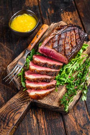 Photo pour Sliced grilled duck meat breast fillet steak. Dark wooden background. Top view - image libre de droit