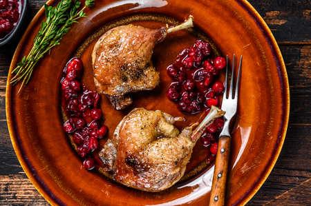 Photo pour Roasted Christmas duck legs with cranberrie sauce. Dark wooden background. top view - image libre de droit