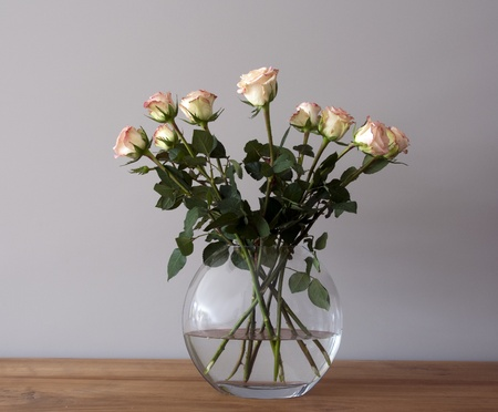 bouquest of roses in a vase on wooden table