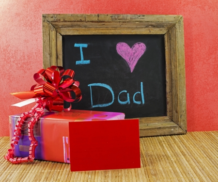 happy fathers day with present and blackboard with text i love dad
