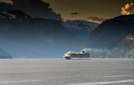 VIK,NORWAY, 25-07-2017,: cruise ship is cruising over the sognefjord at 25-07-2017, the boat is crossing the vilage of Vik ,one of the oldets vilages at the fjord