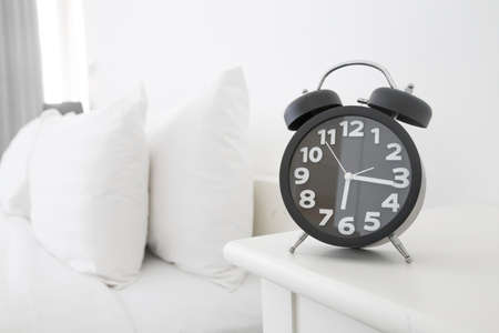 Black alarm clock and bed