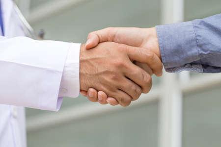 Photo pour Doctor shakes hands with a patient - image libre de droit