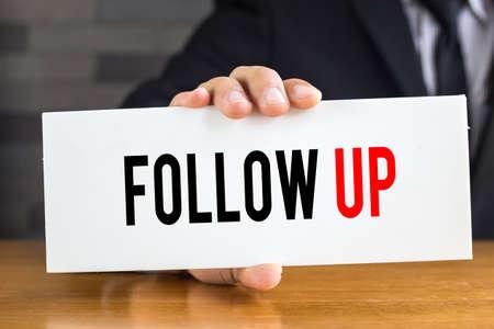 Photo pour Follow up, message on white card and hold by businessman - image libre de droit