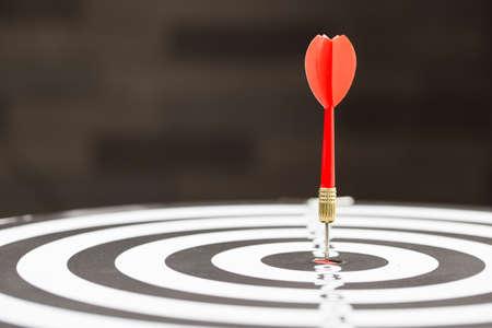 Target dart arrow hitting in the target center of dartboard