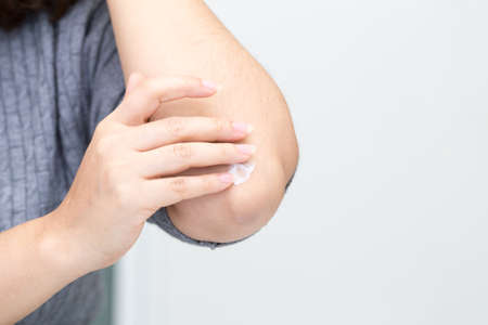 Photo pour Closeup of young woman applying cream on elbows - image libre de droit