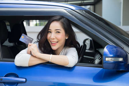 Photo pour Happy beautiful Asian woman sitting inside new car blue and showing credit card pay for oil, pay a tire, maintenance on the garage, Make payment for refueling car on gas station, Automotive financing - image libre de droit