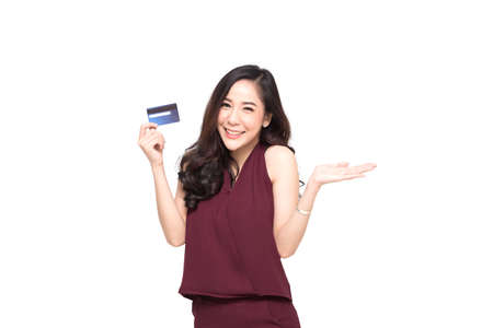 Foto de Young smiling beautiful Asian woman presenting credit card in hand for making payment shopping isolated on white background - Imagen libre de derechos