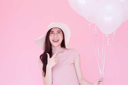 Happy beauty girl laughing with white balloons on pink background, Young woman celebrating on birthday party or having fun in holiday, Asian thai model