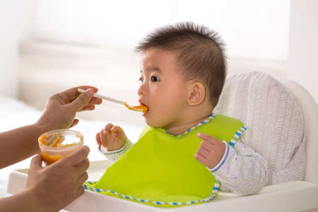 Photo pour Mom is feeding liquid food to her Asian son - image libre de droit