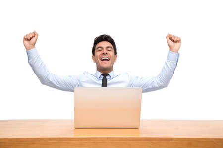 Photo for Excited handsome businessman feeling winner celebrating victory online business success and sitting on desk with laptop isolated on white background - Royalty Free Image