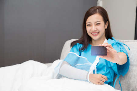 Photo pour Asian woman holding insurance cards and wear patient suits on the arms wearing soft splint sitting on bed at hospital - image libre de droit