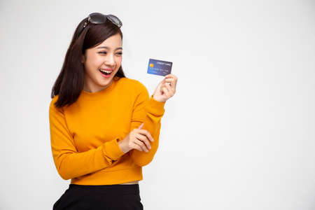 Foto de Happy Asian woman in yellow shirt holding credit card or cash advances, Pay instead of money and specially curated benefits for lady card concept - Imagen libre de derechos