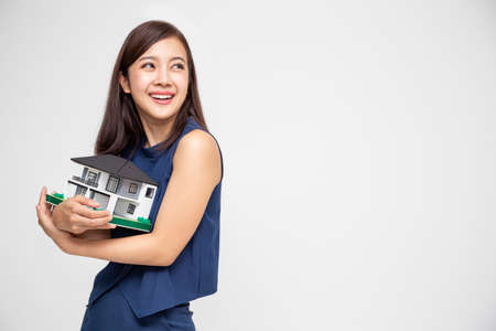 Foto de Young Asian woman smiling and hugging dream house sample model isolated over white background, Real estate and home insurance concept - Imagen libre de derechos