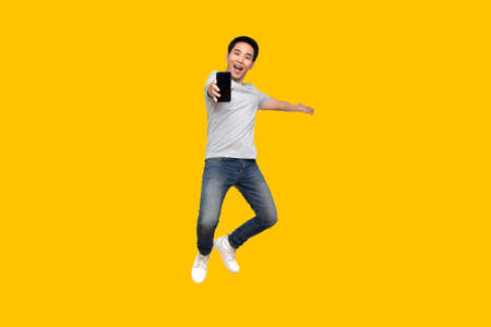 Photo pour Asian man jumping and presenting mobile phone isolated on yellow background - image libre de droit