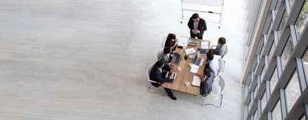 Foto de Top view of group of multiethnic busy people working in an office, Aerial view with businessman and businesswoman sitting around a conference table with blank copy space, Business meeting concept - Imagen libre de derechos