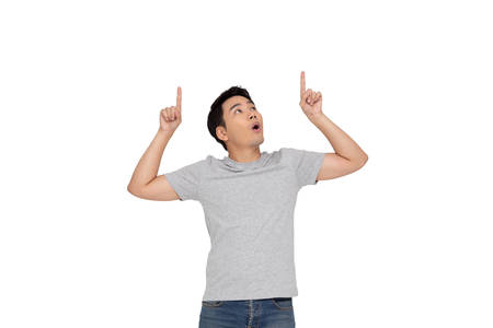 Photo pour Portrait of a happy Asian young man pointing fingers up at copy space isolated over white background - image libre de droit