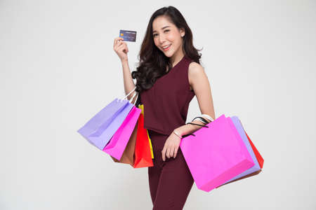 Photo pour Portrait of a happy young Asian women in red dress holding shopping bags and credit card isolated over white background, Year end sale or mid year sale promotion clearance for Shopaholic concept - image libre de droit