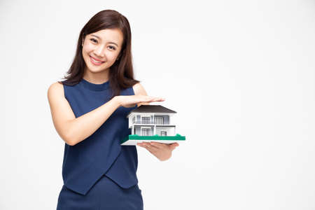 Photo pour Portrait of beautiful young Asian woman with hands protecting house or home model isolated on white background, Real estate and home insurance concept - image libre de droit
