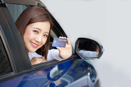 Photo for Happy young Asian woman holding payment card or credit card and used to pay for gasoline, diesel, and other fuels at gas stations, Driver with fleet cards for refueling car - Royalty Free Image