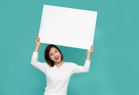 Foto de Young attractive asian woman showing and holding blank white board, Showing empty board for input your text - Imagen libre de derechos