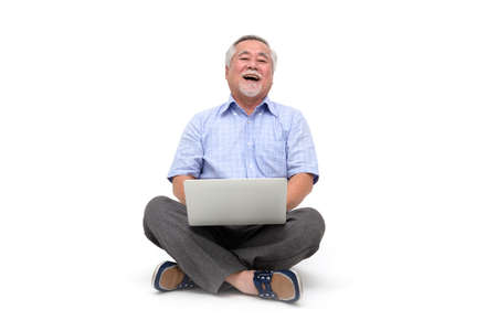 Photo for Excited senior asian man feeling happy celebrating victory online business success and sitting on floor with laptop isolated on white background, Freelance mature concept - Royalty Free Image