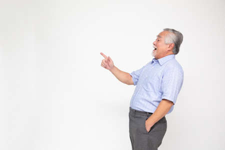 Photo for Smiling senior man pointing towards something, Happy Asian old man showing to copy space blank space isolated on white background - Royalty Free Image