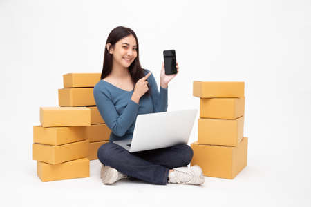 Photo for Young asian woman startup small business freelance holding parcel box, mobile phone and computer laptop and sitting on floor isolated on white background, Online marketing packing box delivery concept - Royalty Free Image