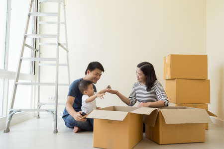 Photo pour Happy Asian family with cardboard boxes in new house at moving day, Real estate and home concept - image libre de droit