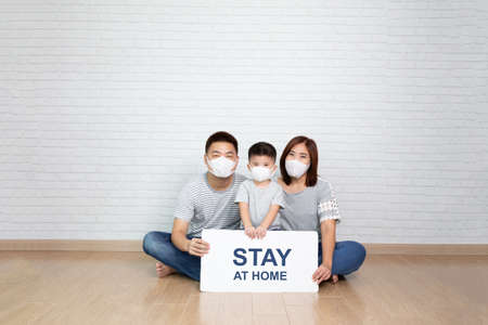 Photo pour Asian family wearing protective medical mask for prevent virus Covid-19 holding white paper with stay at home on hand and sitting together on floor at home - image libre de droit