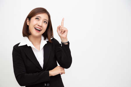 Photo pour Smiling asian business woman pointing up isolated over white background - image libre de droit