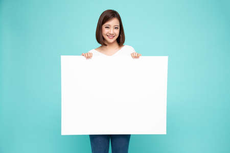 Photo for Young asian woman showing and holding blank white billboard isolated on green background - Royalty Free Image