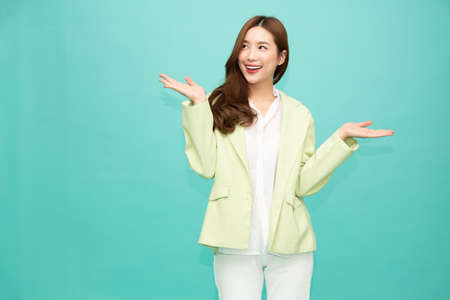 Photo pour Happy Asian woman presenting or showing open hand palm with copy space for product isolated over green background - image libre de droit