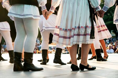 Photo pour Traditional romanian dancers in traditional costumes hand in hand on stage - image libre de droit