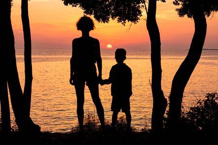 Foto de Mother and her child watching beautiful sunset on the seashore - Imagen libre de derechos