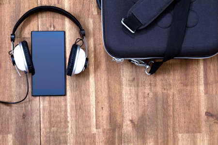 Cellphone with headphone and a briefcase background