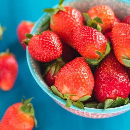 Foto de red strawberries in the plate isolated on wooden table - Imagen libre de derechos