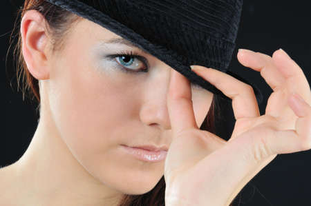 alluring girl hold on the hat two fingers