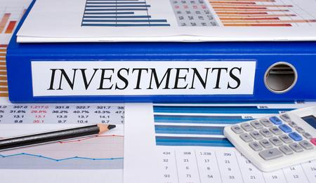 Photo pour Investments blue binder in the office - image libre de droit