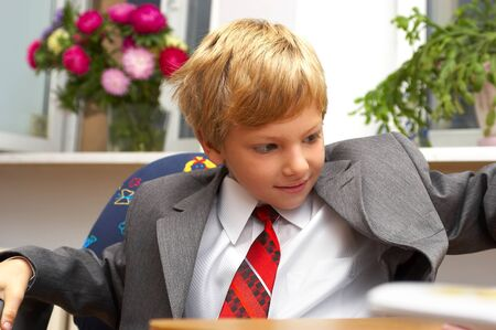 The boy in a suit behind a desk