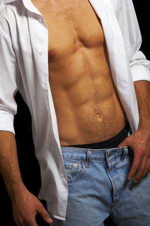 Muscular male torso on a black