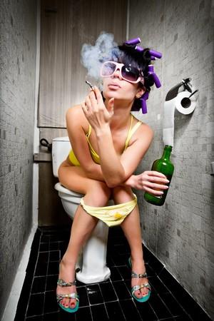 Foto de girl sits in a toilet with an alcohol bottle - Imagen libre de derechos