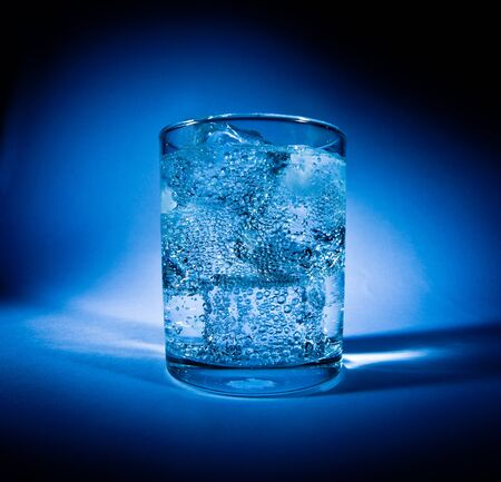 Glass of water with ice on a dark blue background