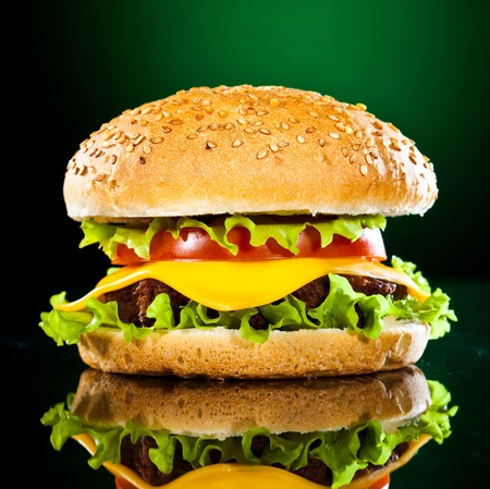 Photo for Tasty and appetizing hamburger on a darkly green background - Royalty Free Image